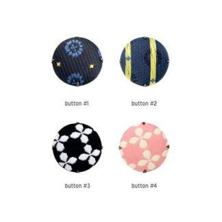 De Geursystemen voor thuis Aroma button kan gedragen door een vrouw in donkerblauwe jurk met kop koffie in haar handen. De aroma button geeft geur af en kan gedragen worden op uw kleding