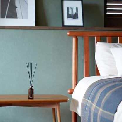 Stick diffuser geplaatst naast houten bed op een bijzettafel